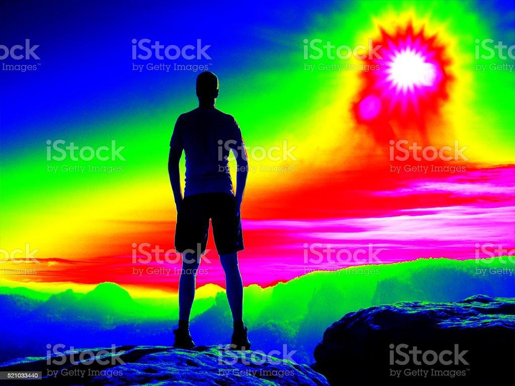 Man on rocky peak. Fantastic infrared scan. Mist morning valley stock photo