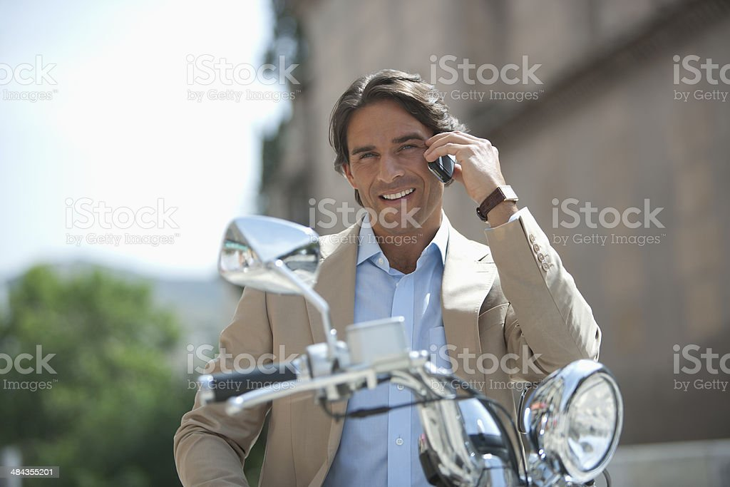 Man on scooter and using a cell phone stock photo