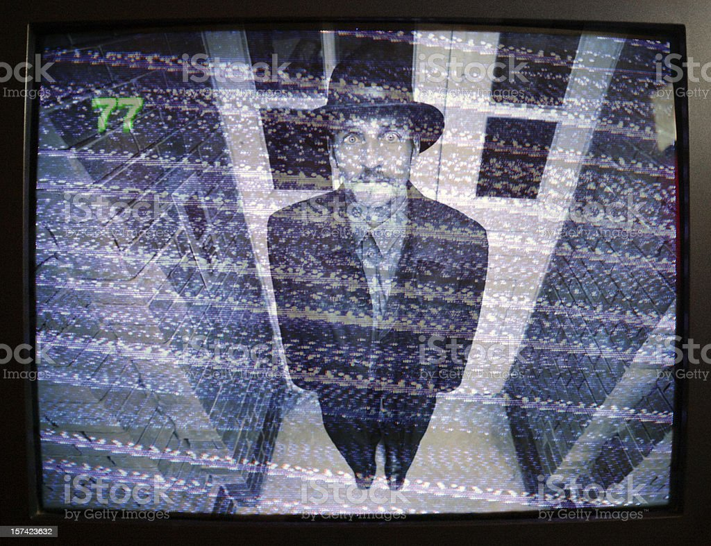 man on security monitor stock photo