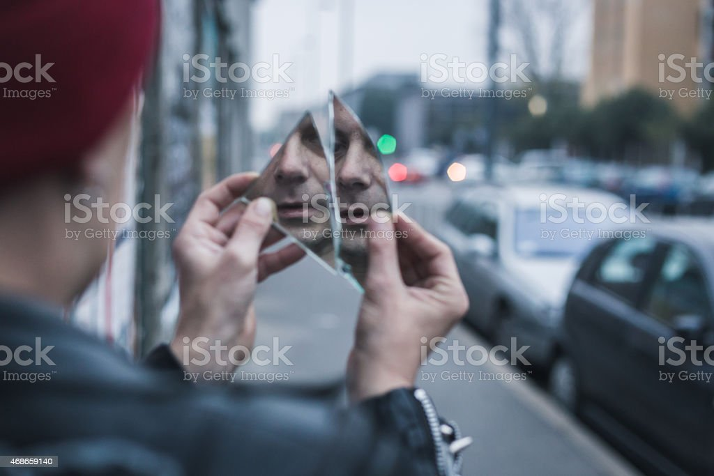 Man on sidewalk looking at him self in a shattered mirror  stock photo