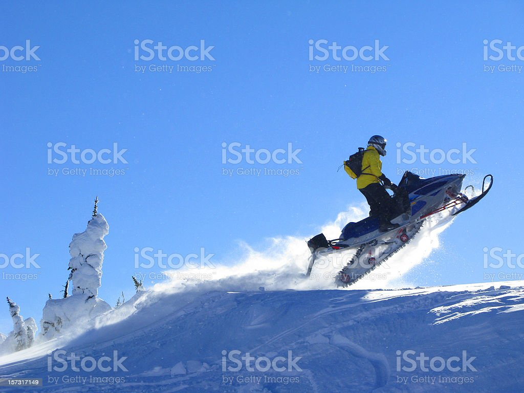 Man on snowmobile jumping on hilltop stock photo