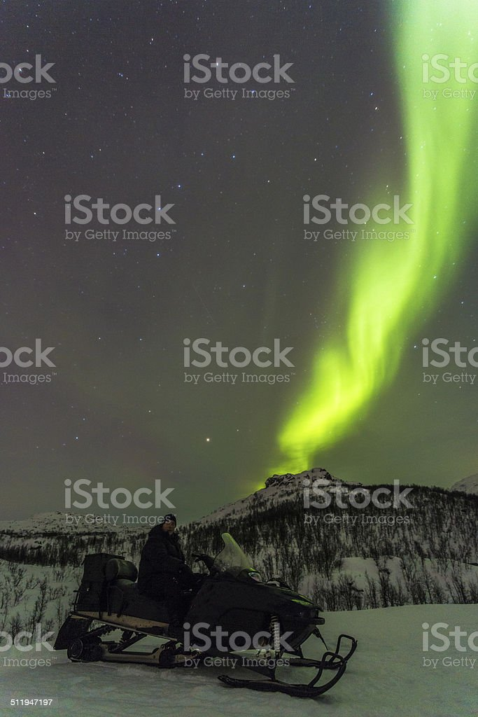 Man on snowmobile watching Northern light stock photo