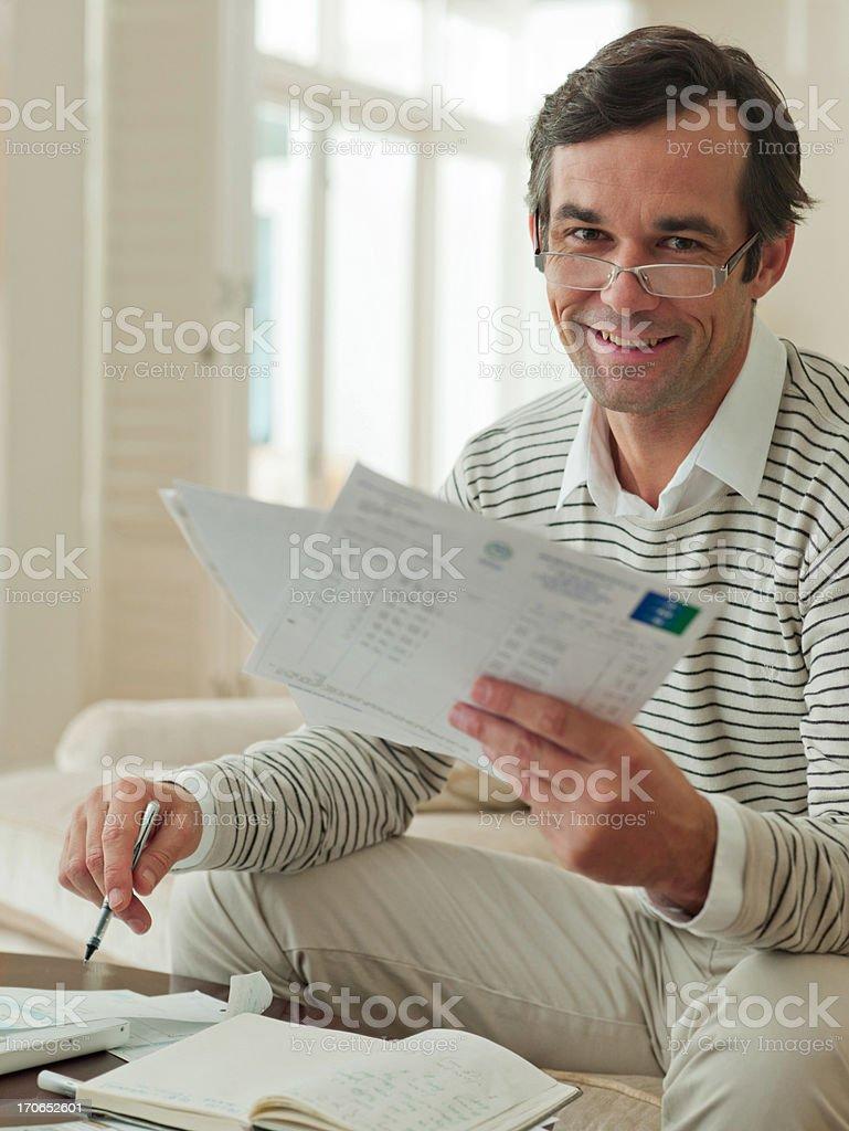 Man on sofa examining paperwork royalty-free stock photo