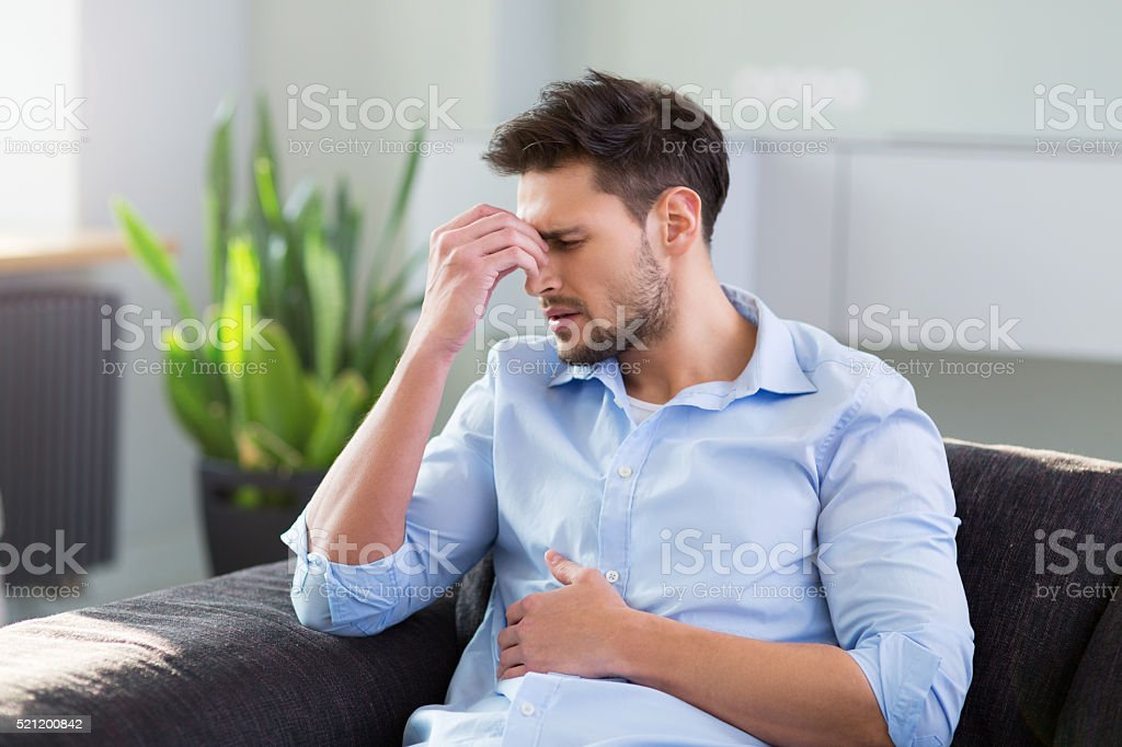 Man On Sofa Having Headache stock photo
