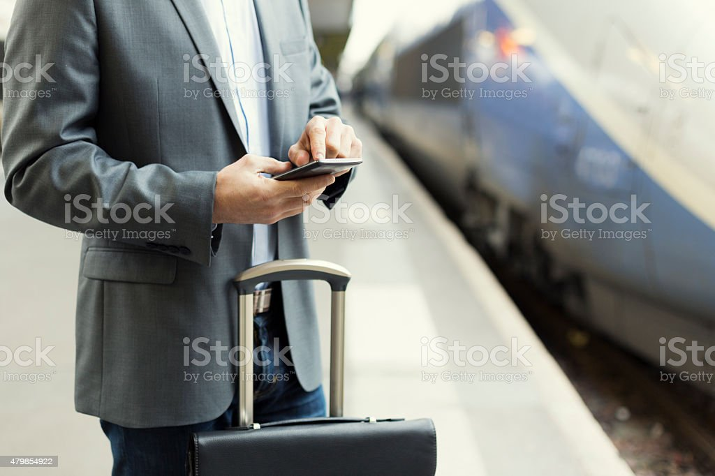 Man on station platform typing text on mobile phone stock photo