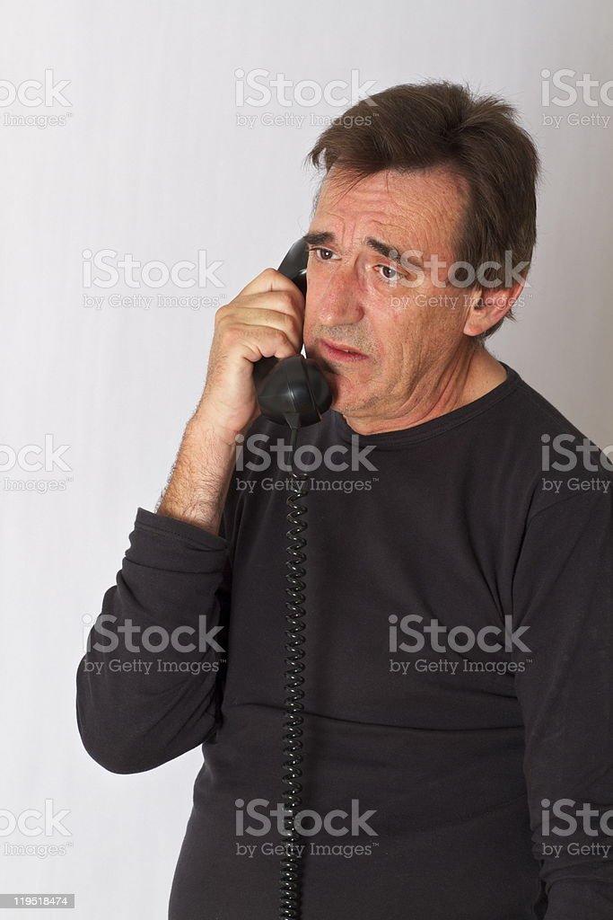 Man On Telephone Looking Cresftallen And Sad stock photo