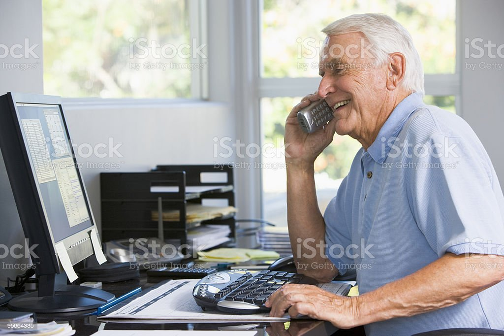 Man on telephone using computer smiling royalty-free stock photo