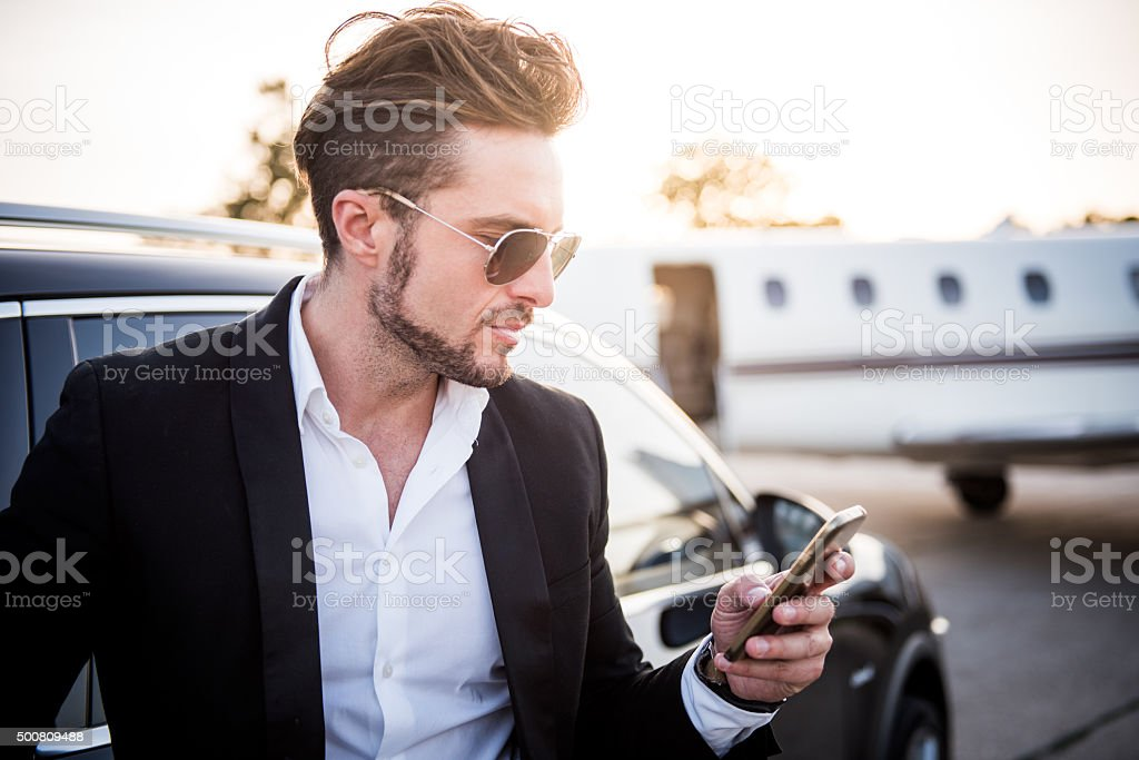 Man on the airport holding mobile phone stock photo