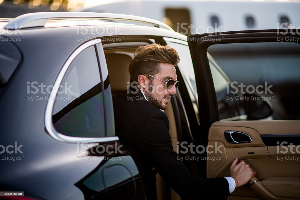 Man on the airport opening car door stock photo