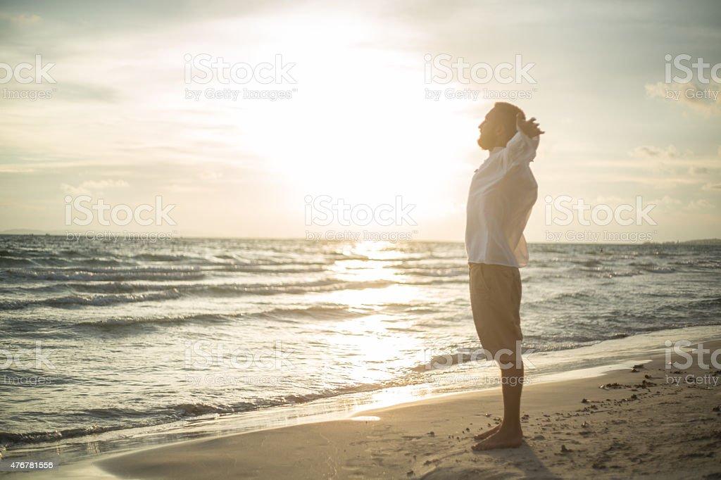 Man on the beach enjoying nature and freedom stock photo