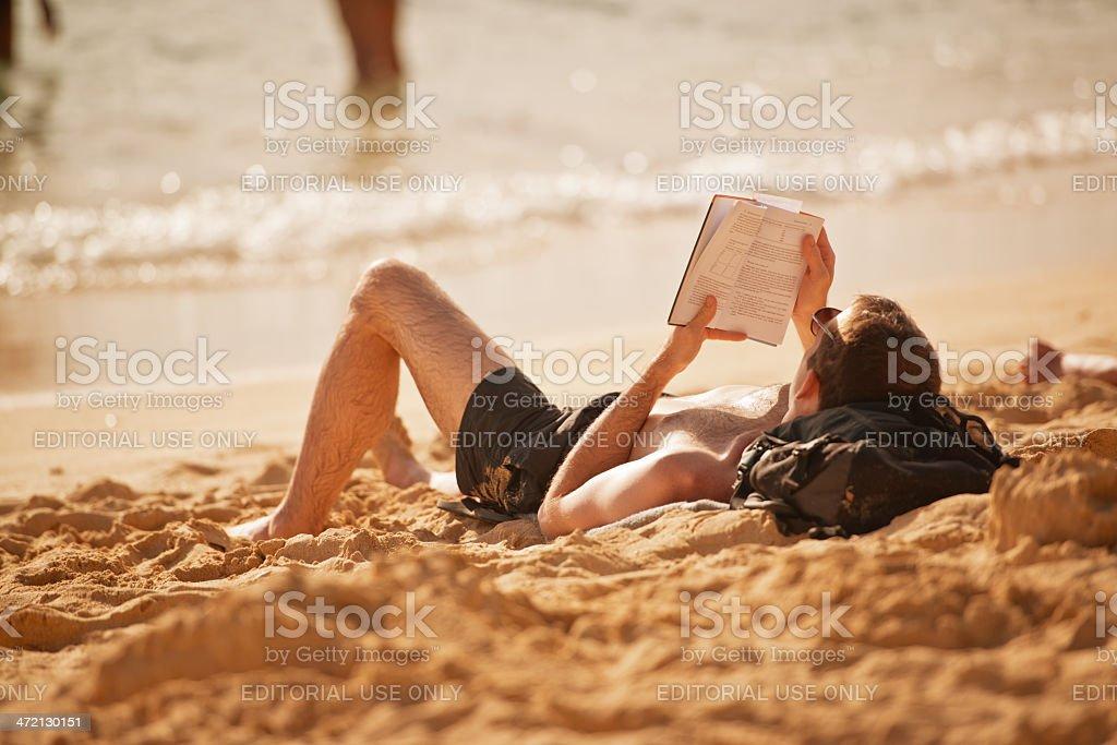 Man on the beach reading  book stock photo