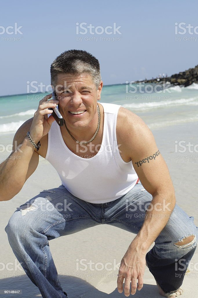 Man On The Beach Using A Phone royalty-free stock photo