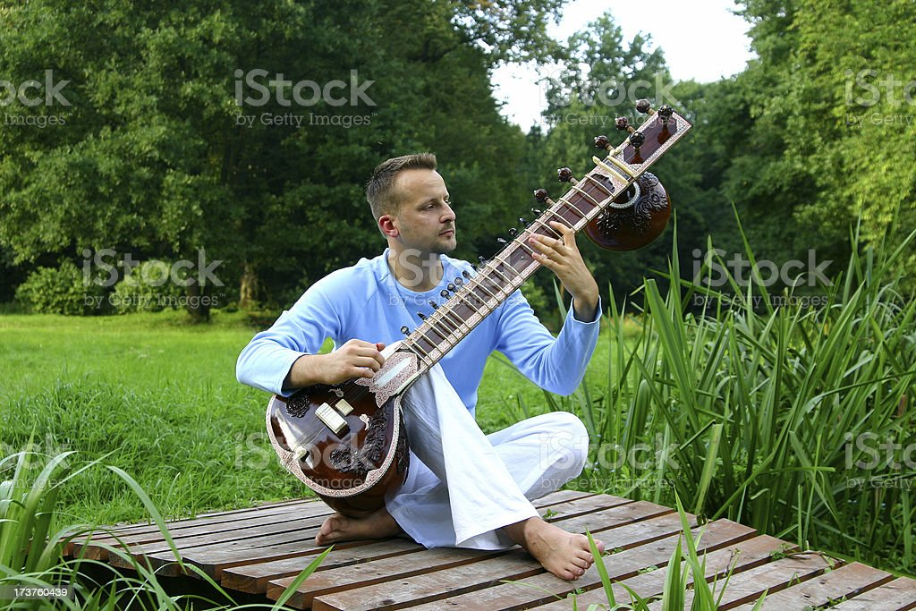 man on the breastbone with sitar stock photo