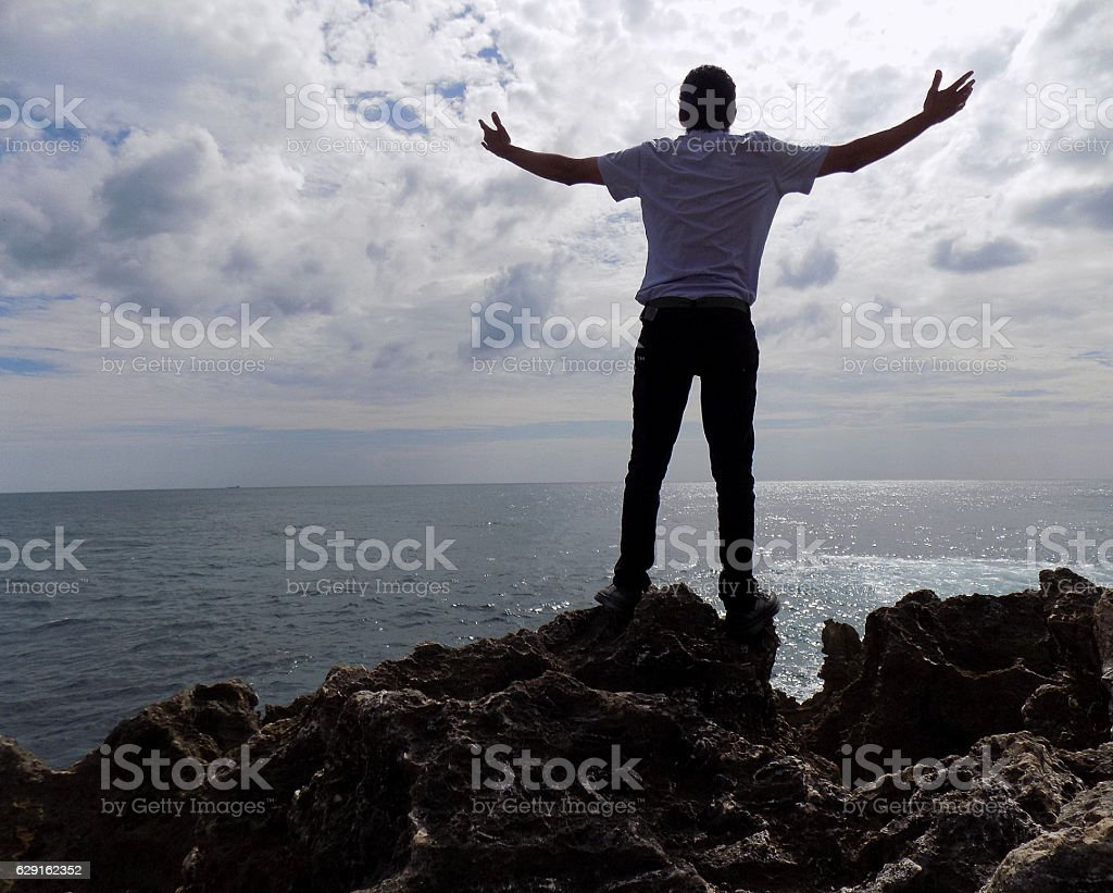Man on the coast with open arms stock photo