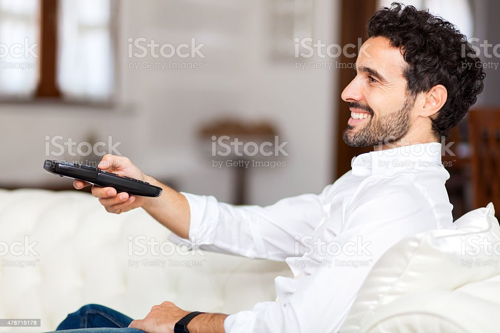 Man on the couch switches remote control TV channels stock photo