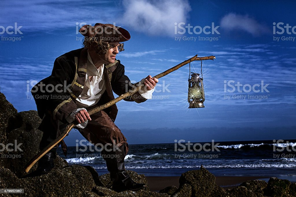 Man on the edge of a cliff holding a lantern stock photo