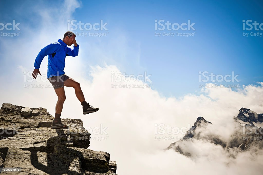 man on the edge of the abyss stock photo