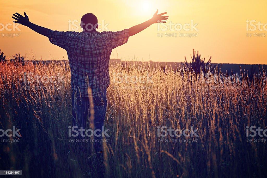 Man on the meadow prays to God stock photo