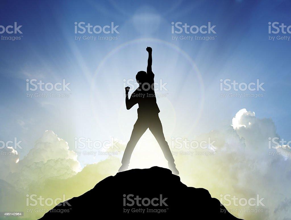 Man on the peak of mountain and sunlight stock photo