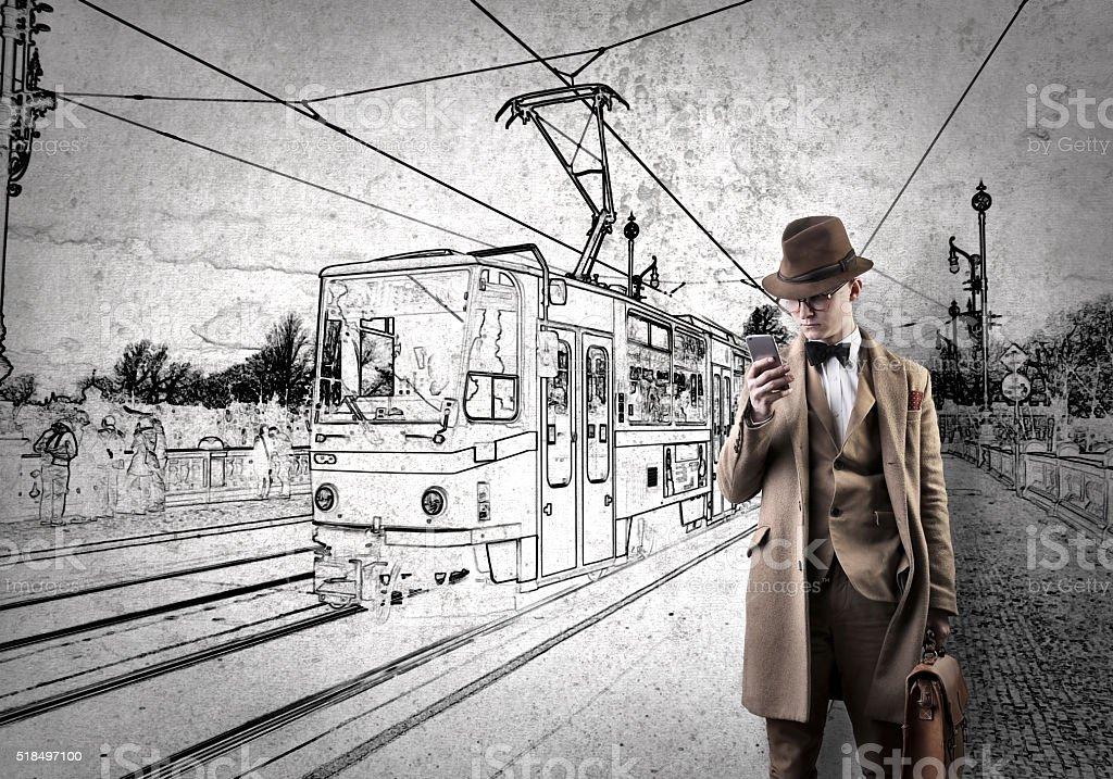Man on the phone passing by a tram stock photo