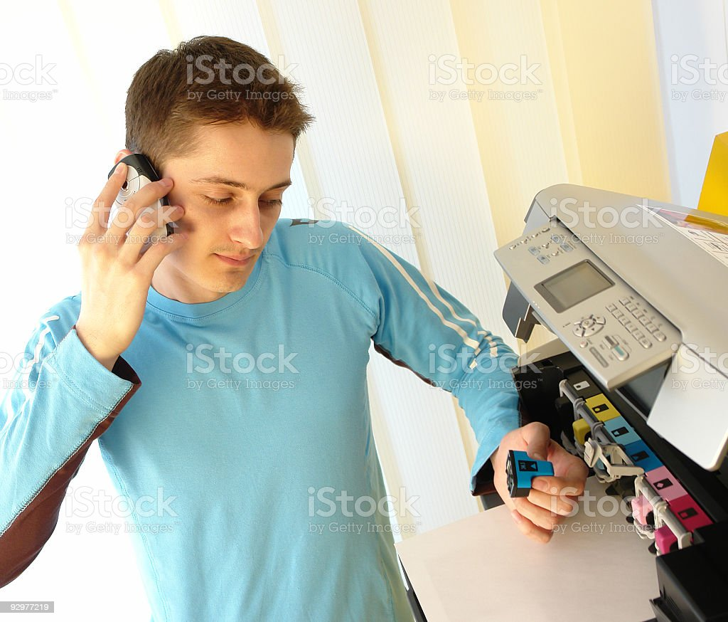 Man on the phone talking about printer problems stock photo