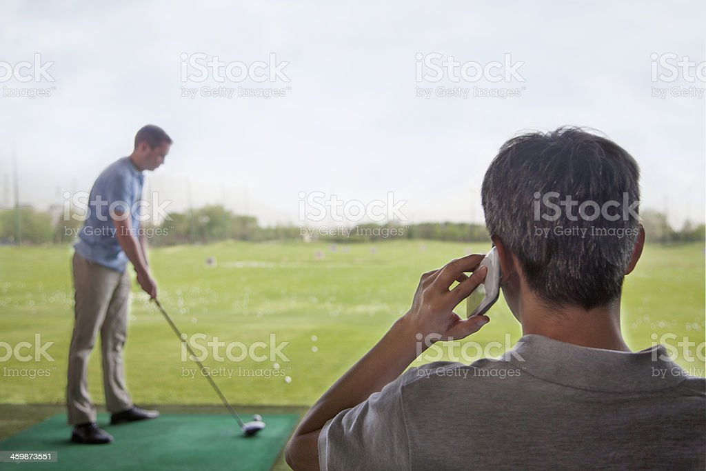 Man on the phone while another plays golf royalty-free stock photo