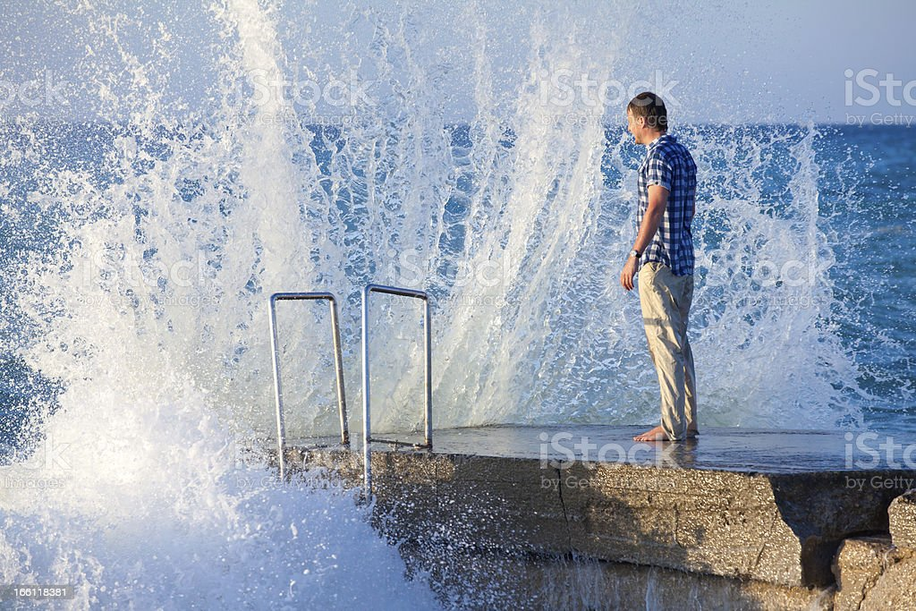 Man on the pier in big wave with splashes royalty-free stock photo