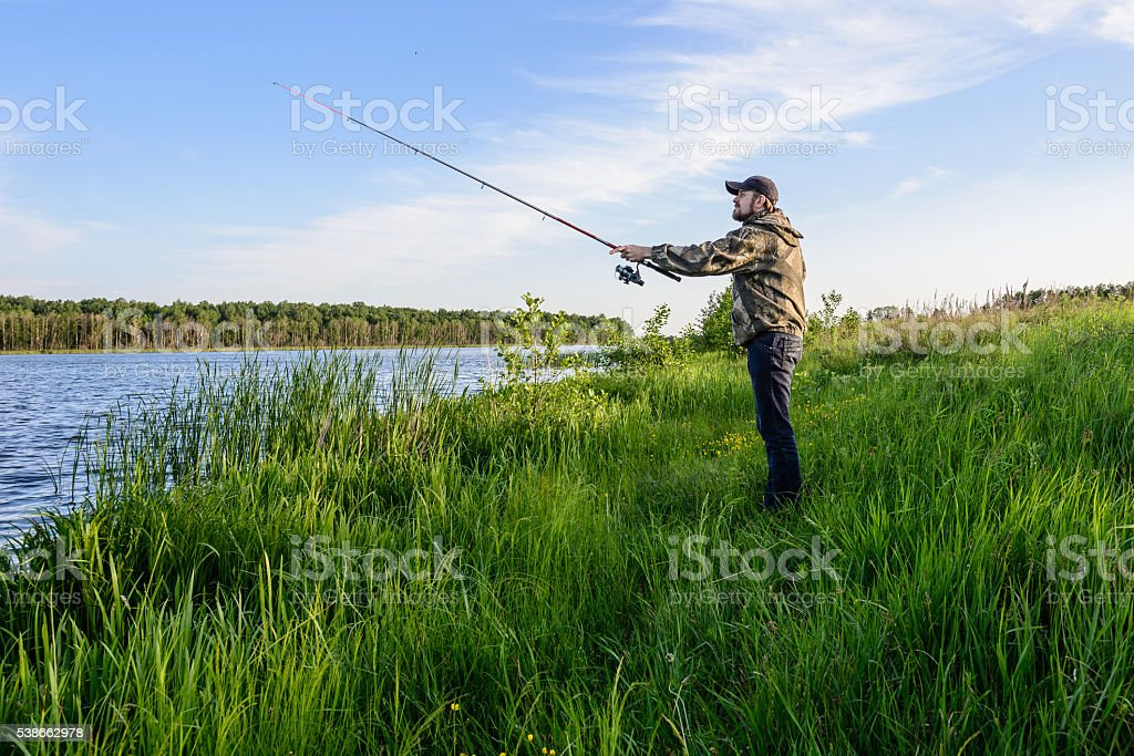 man on the river throws a spinning fishing stock photo