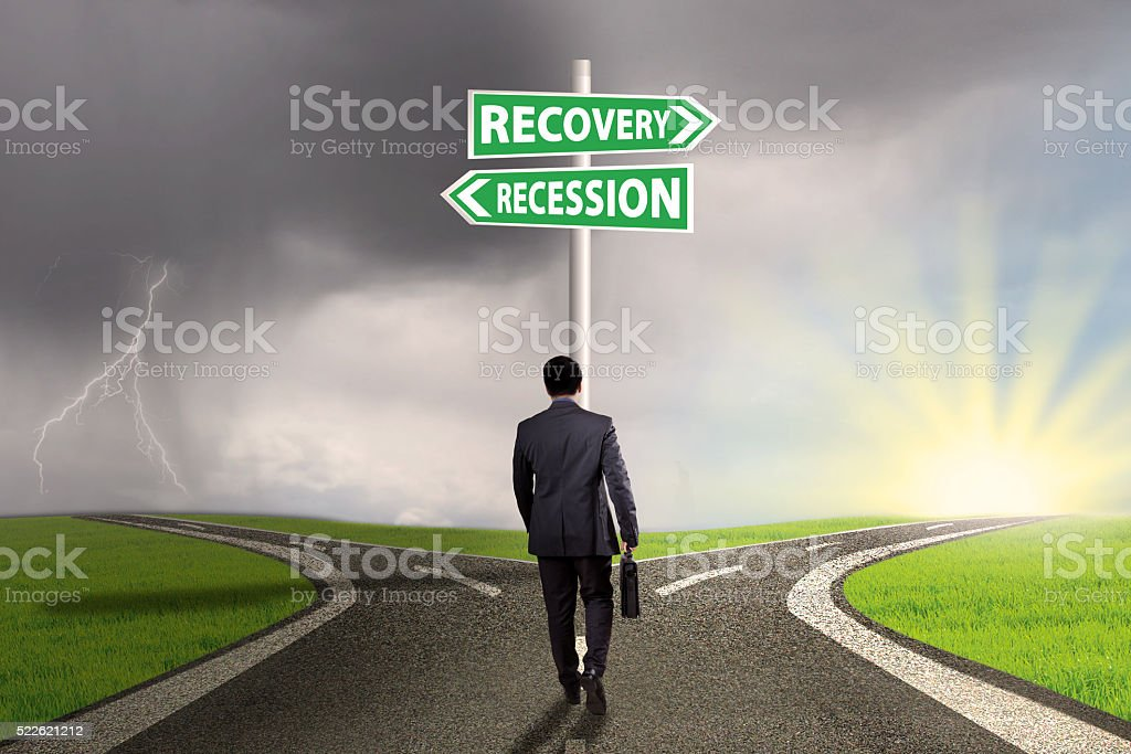 Man on the road with finance signpost stock photo
