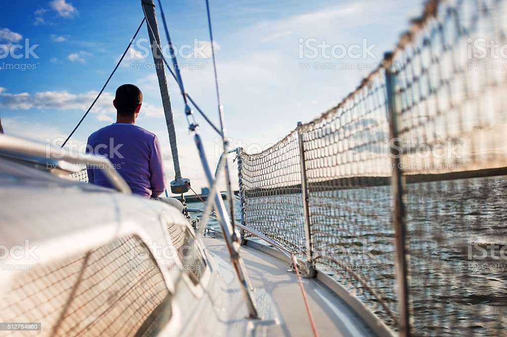 Man on the sailing boat stock photo