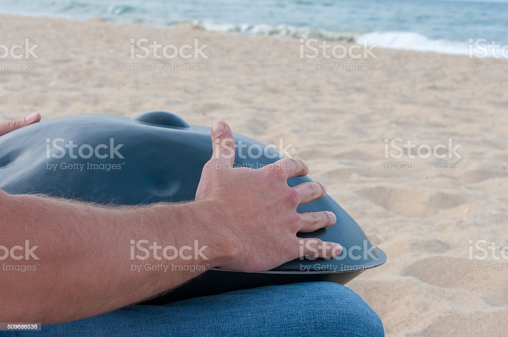 Man on the sand beach playing handpan or hang with stock photo