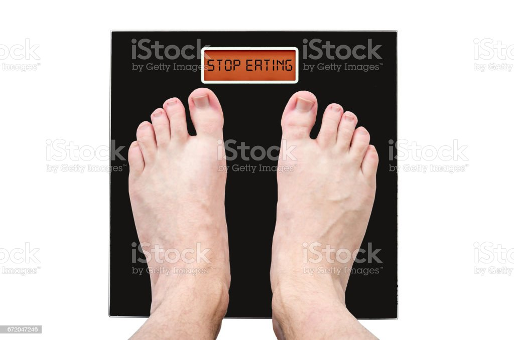 Man on the scales with a lot of weight and health problems, the inscription - stop eating stock photo