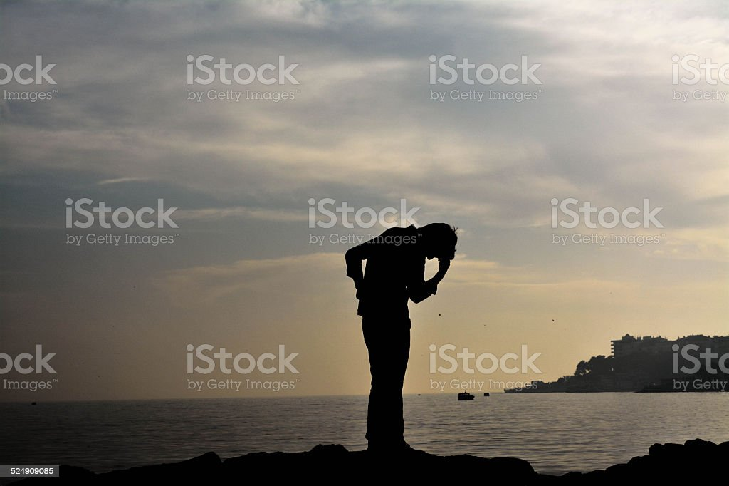 Man on the sea background silhouette: Regrets and sadness stock photo