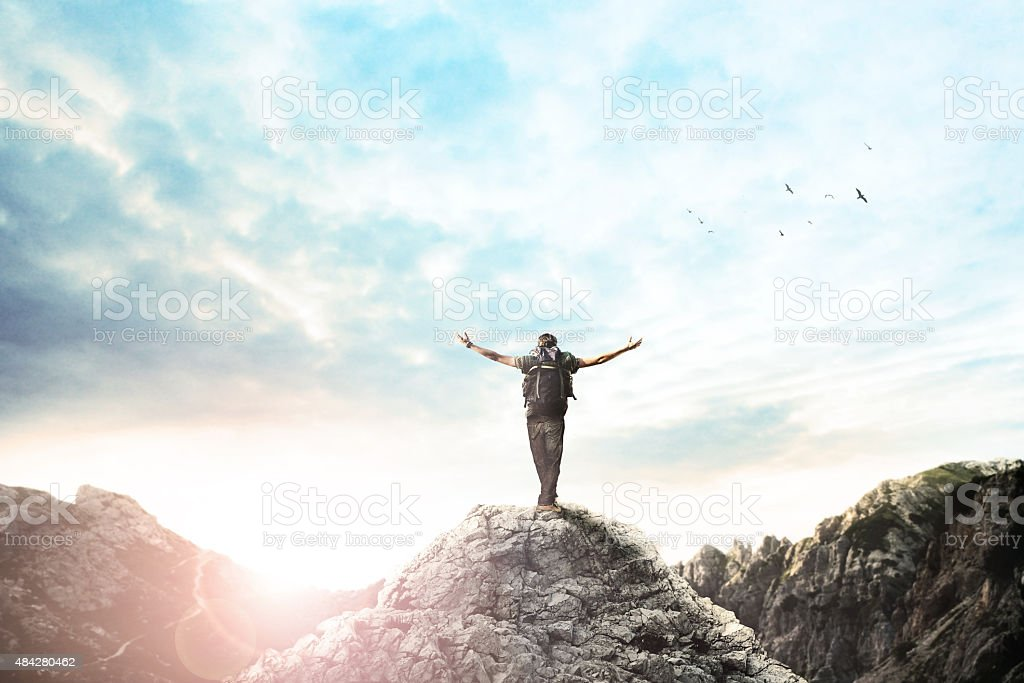 Man on the top of the mountain exulting at sunset stock photo