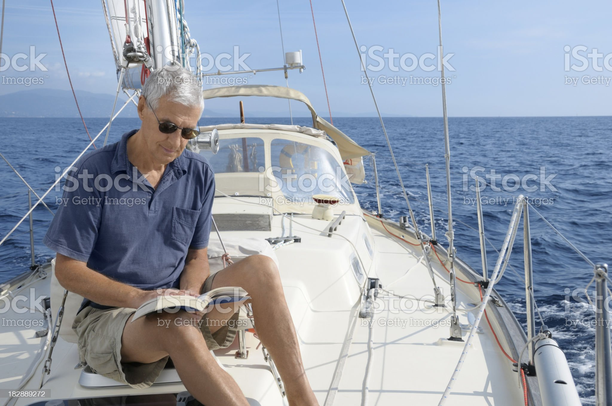 Man on the yacht reading a book royalty-free stock photo