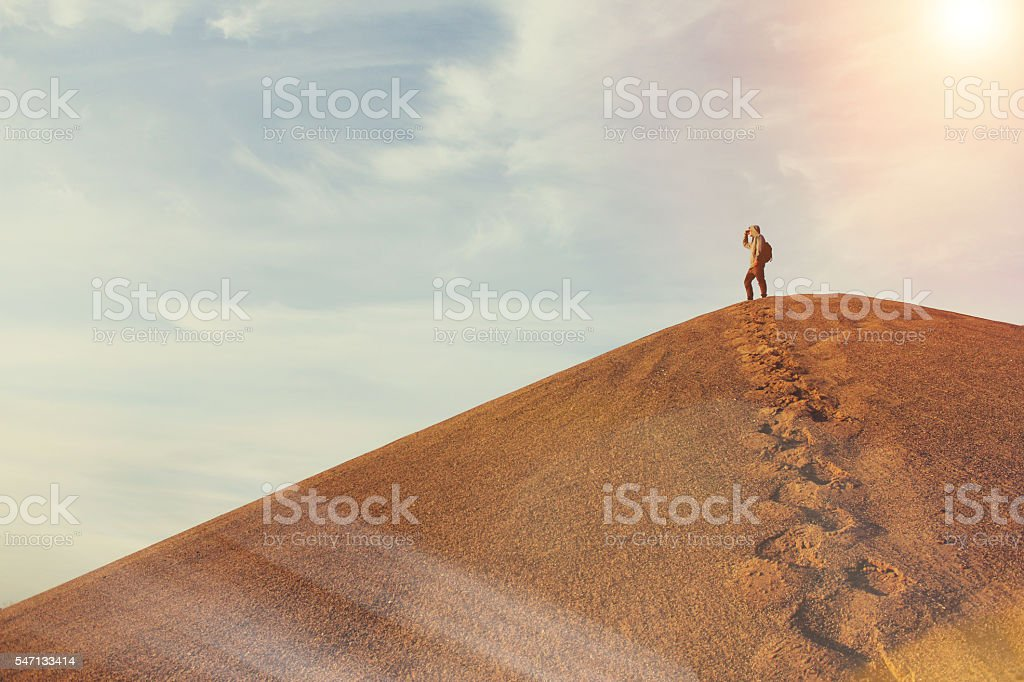 Man on top of a dune in the desert stock photo