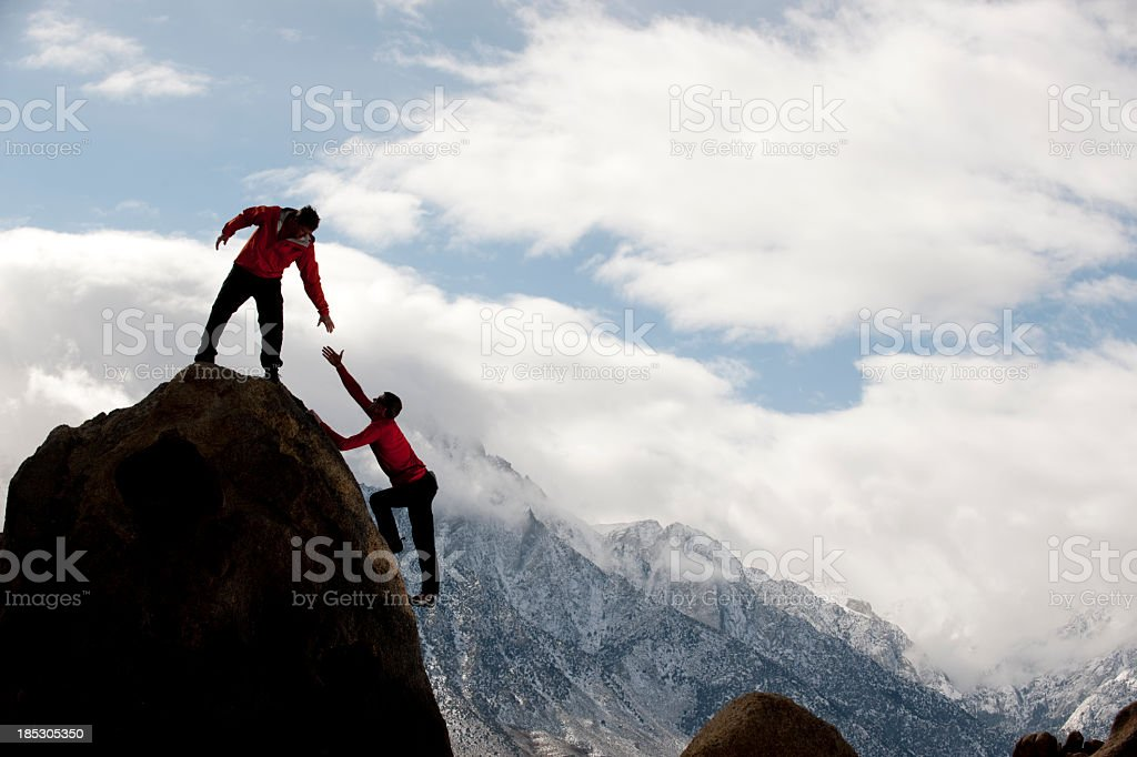 Man on top of mountain helping someone up royalty-free stock photo