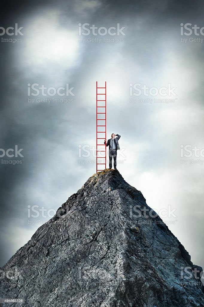 Man On Top Of Mountaintop Looks Up While Holding Ladder stock photo