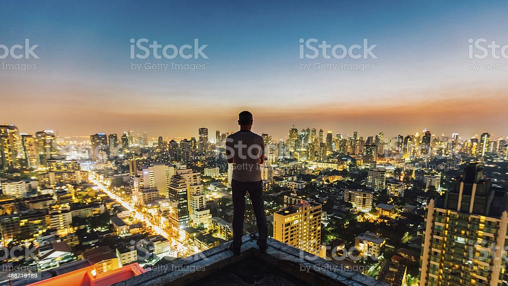 Man on top of skyscraper stock photo