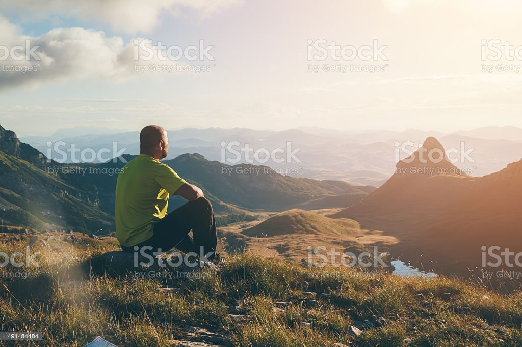 Man on top of the mountain enjoying the landscape stock photo