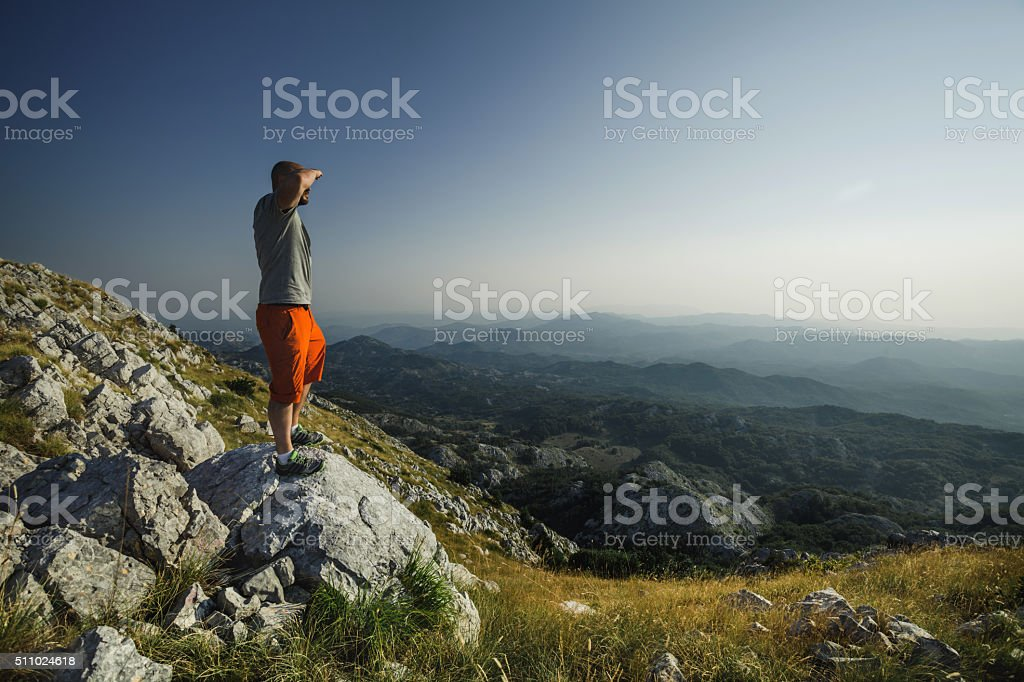 Man on top of the mountain looking ahead stock photo