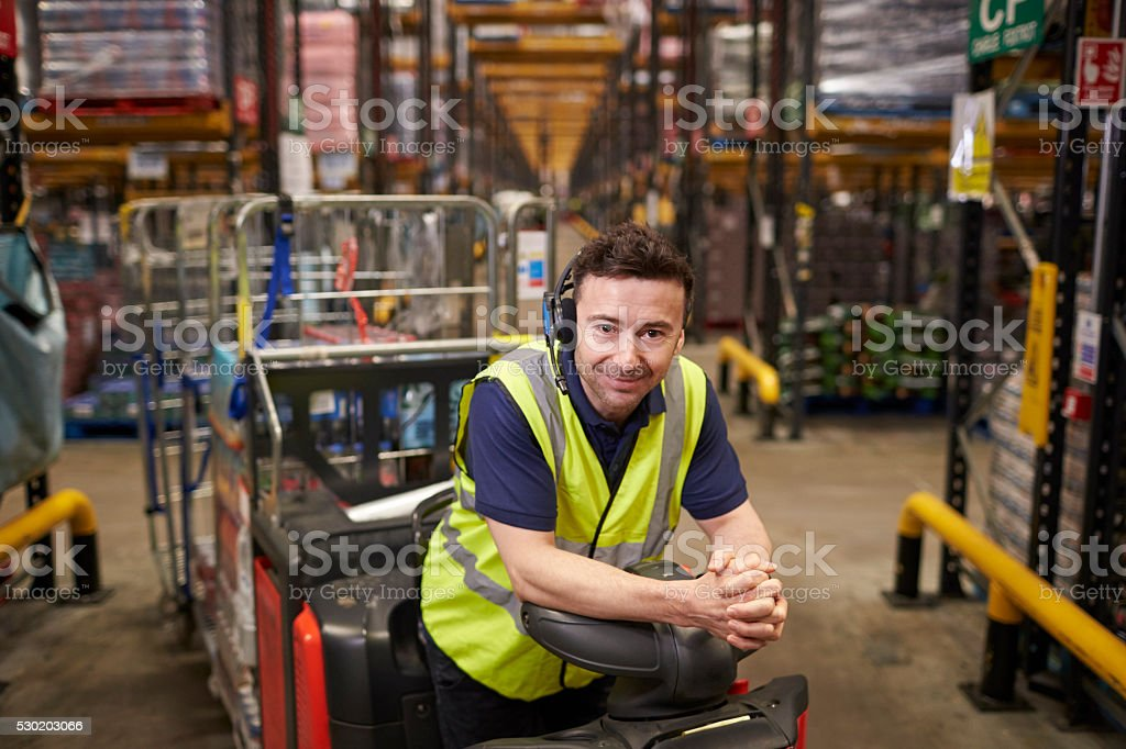 Man on tow tractor in distribution warehouse leans to camera stock photo