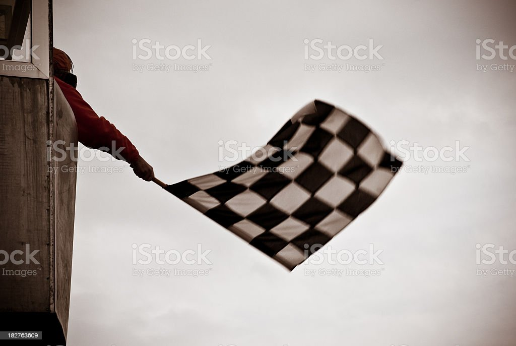 Man on tower waving checkered flag stock photo