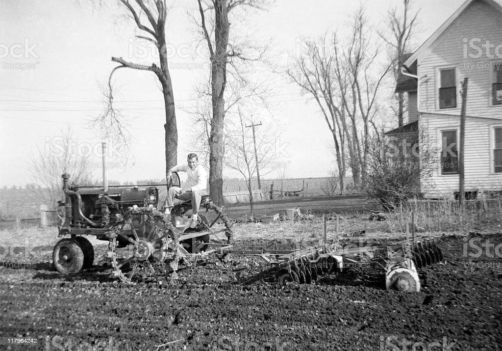 man on tractor disking 1941, retro stock photo