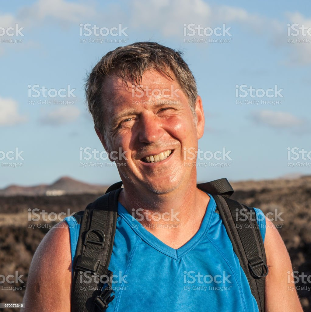 man on walking trail in volcanic area stock photo