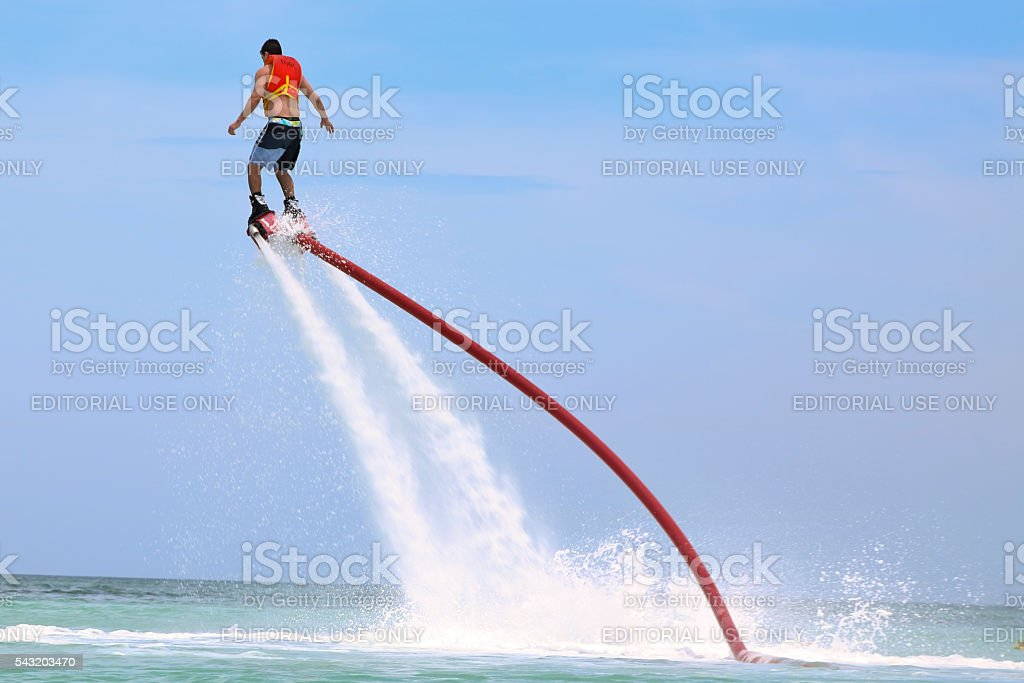 Man on water shoes jet pack in mid air Flyboarding stock photo