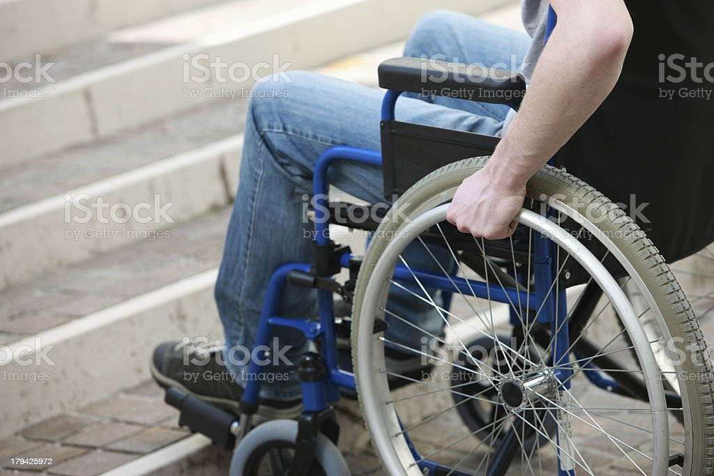 Man on wheelchair facing the challenge of going up on stairs stock photo