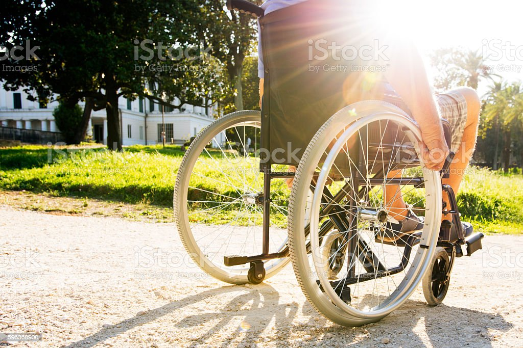 Man on wheelchair in a park stock photo