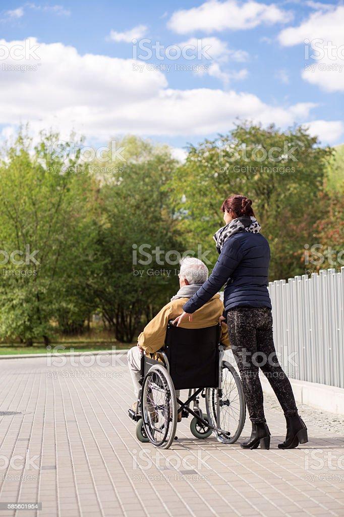Man on wheelchair with nurse stock photo