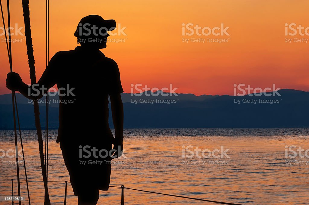 Man on yacht. Bright sunset background. royalty-free stock photo